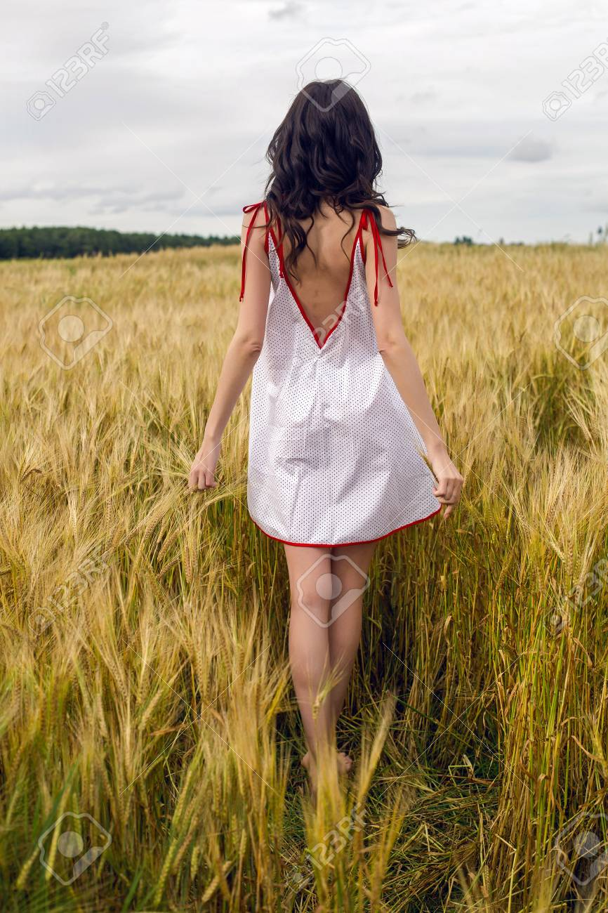 woman in a red light dress stands in a field with yellow dry ears of wheat in the summer - 100361730