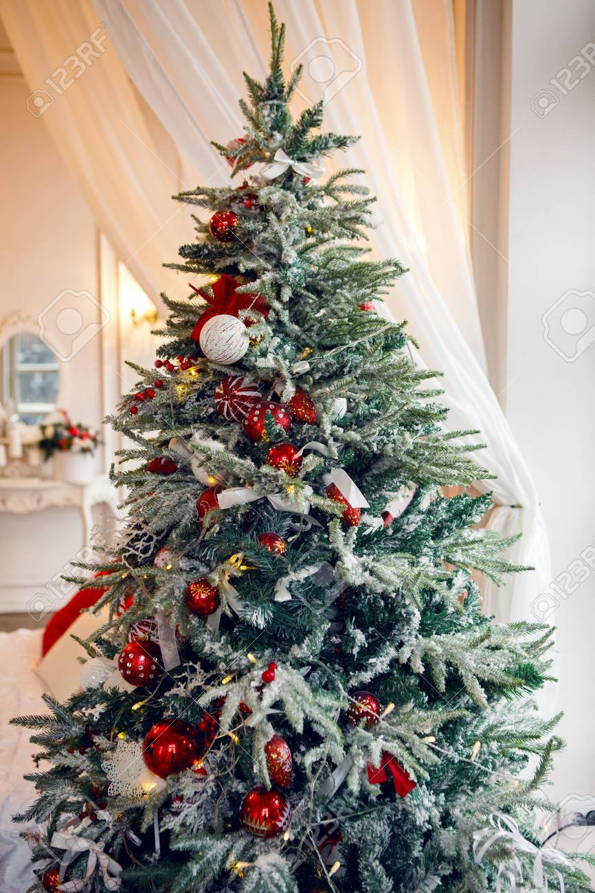 At Home Christmas Trees.Snow Covered Christmas Tree Standing At Home With Red Balls And