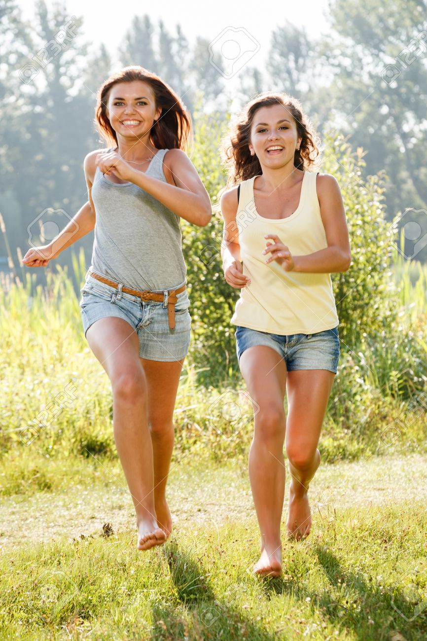 Two Teenage Girls Running On Grass Barefoot Stock Photo, Picture And  Royalty Free Image. Image 24715954.