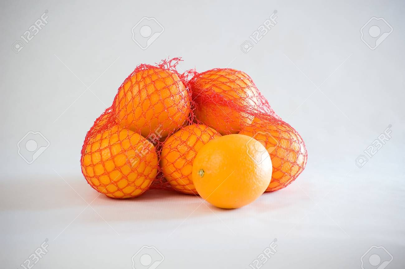 Some fresh oranges in a red net. Stock Photo - 8152160