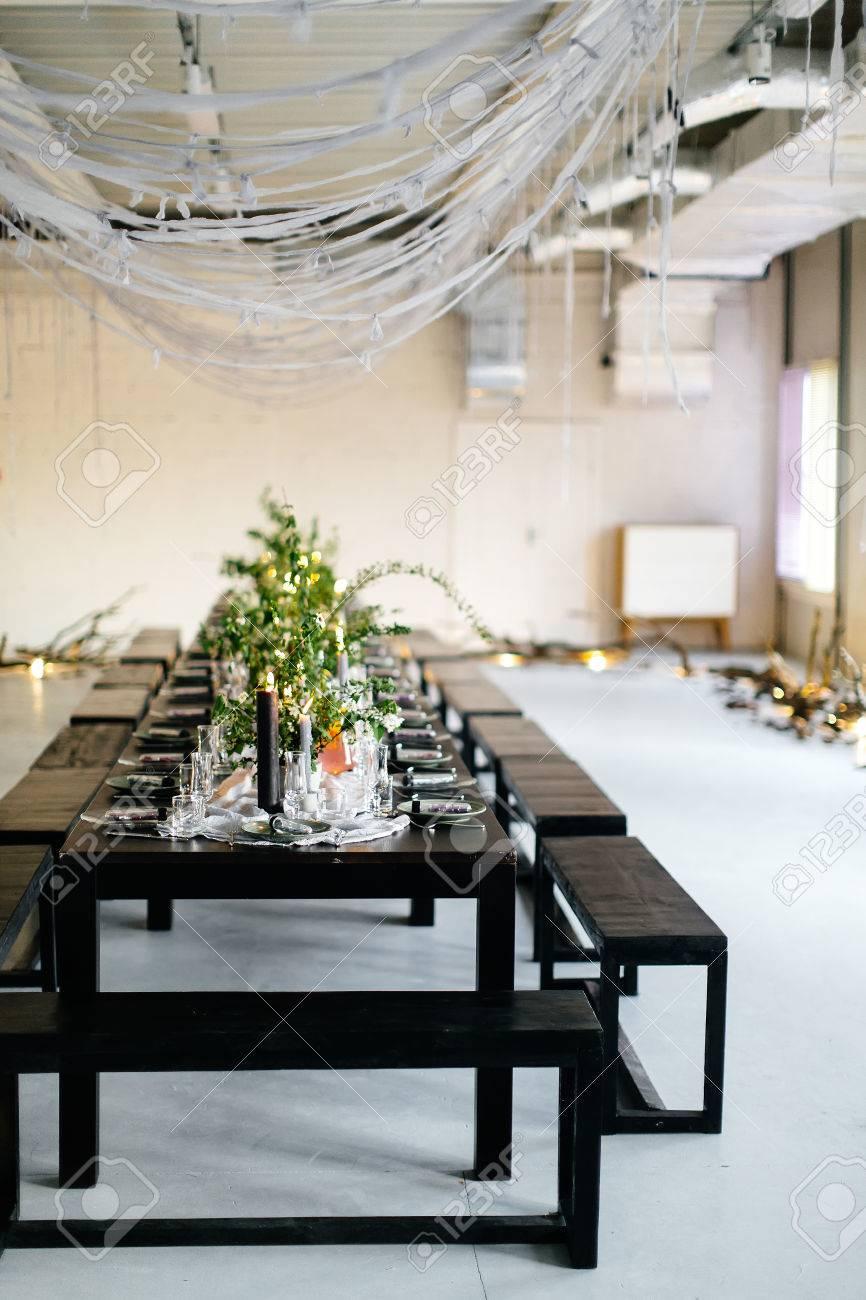 Table élégante, loft. Salle de conception dans le style loft. Table noire,  chaises, vaisselle, bougies. Bocaux avec des verts.