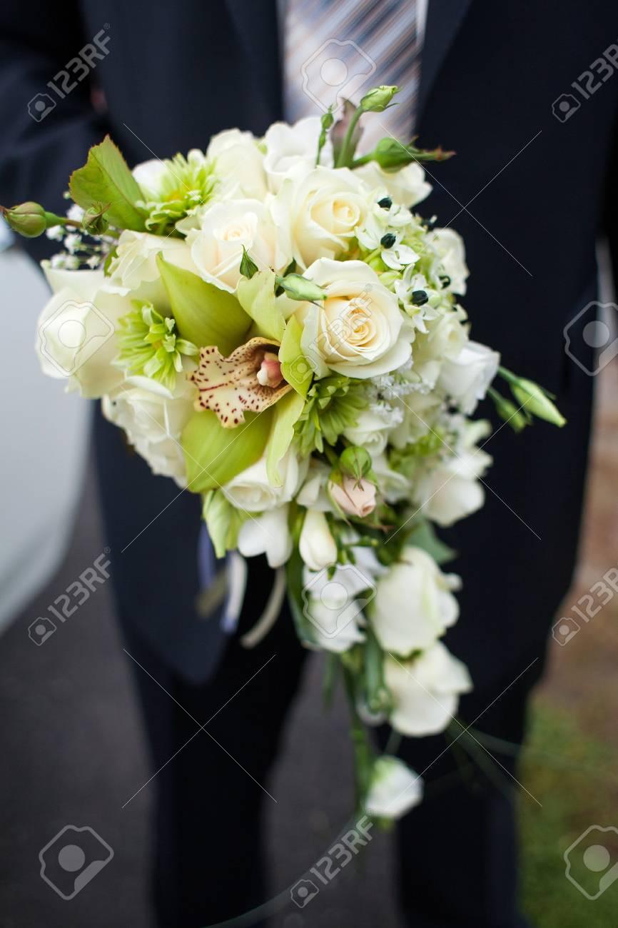 Le Marie Tient Un Bouquet De Roses Et D Orchidees Focus Sur Les Fleurs