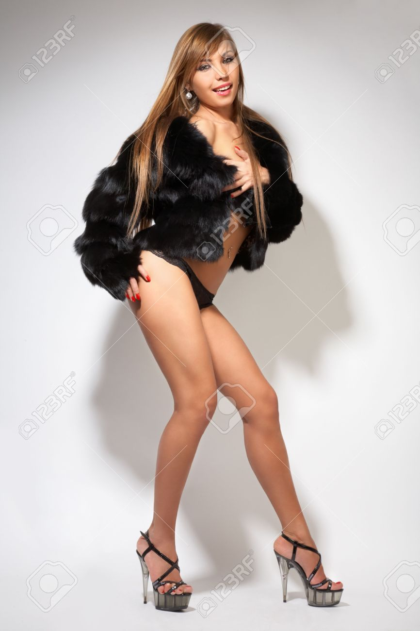 young pretty girl in black fur coat,lingerie and high-heeled shoes on gray Stock Photo - 4783611