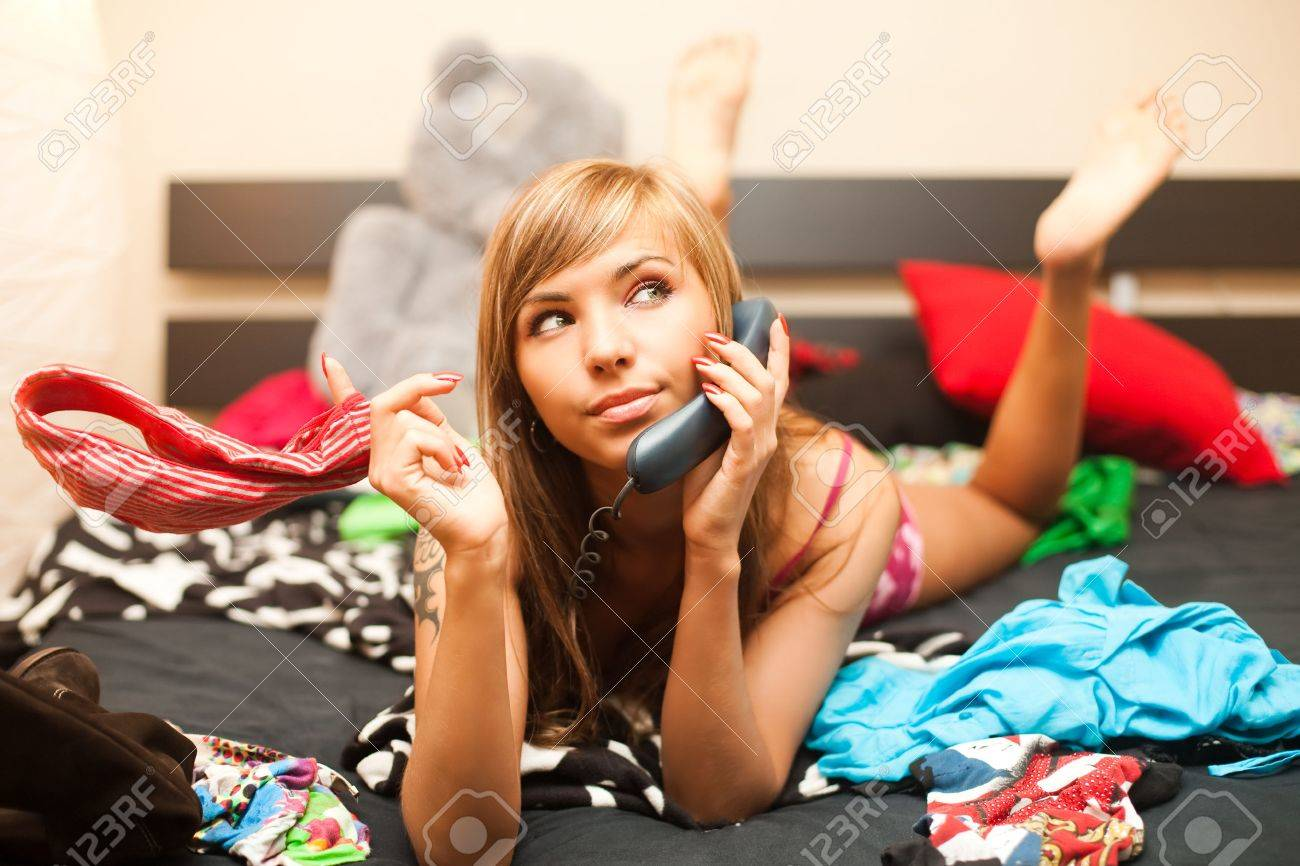 young teen blond woman in bed in chaos of clothes has telephone conversation Stock Photo - 6017144