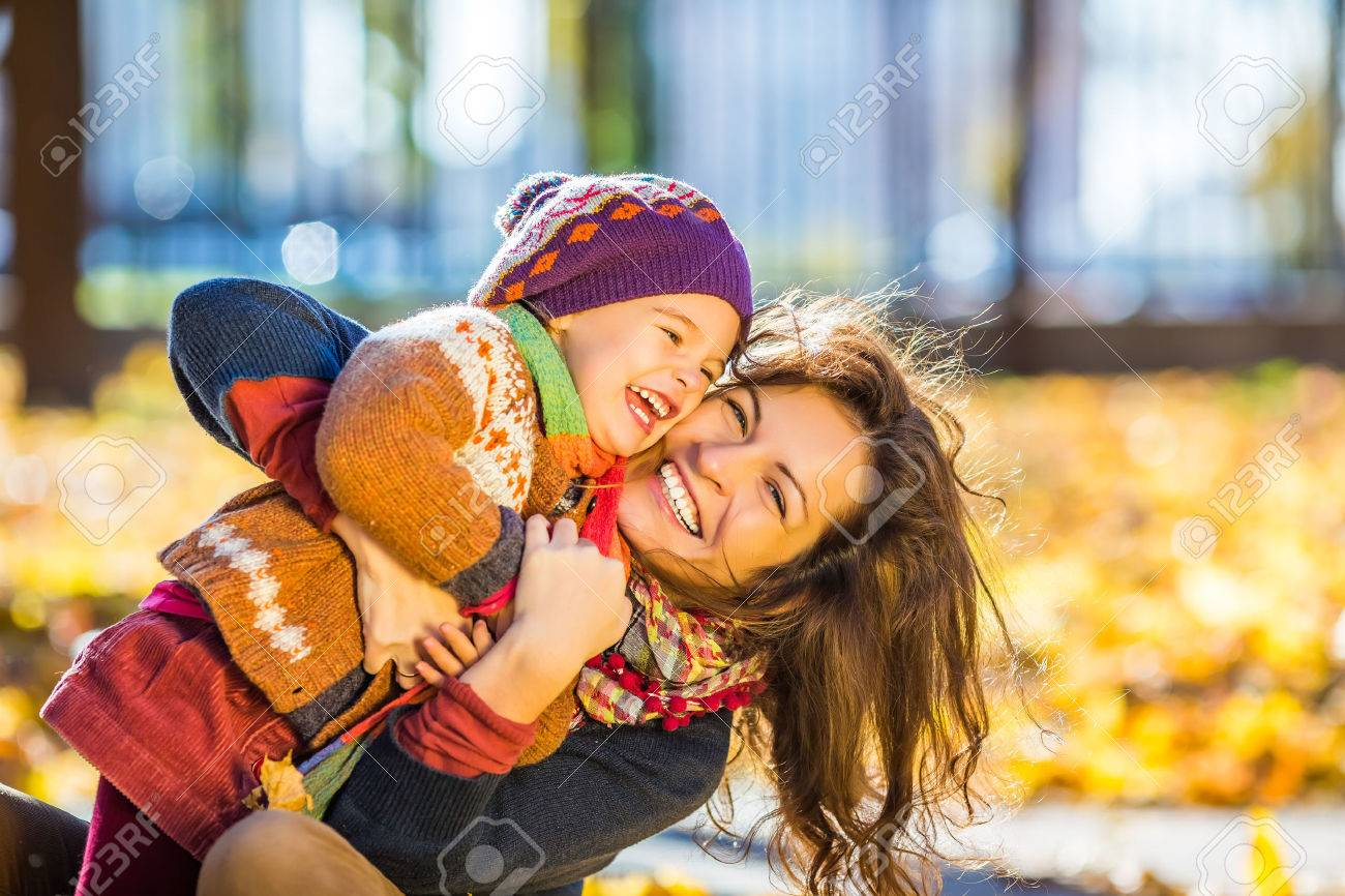 Little girl and her mother playing in the autumn park - 44152307