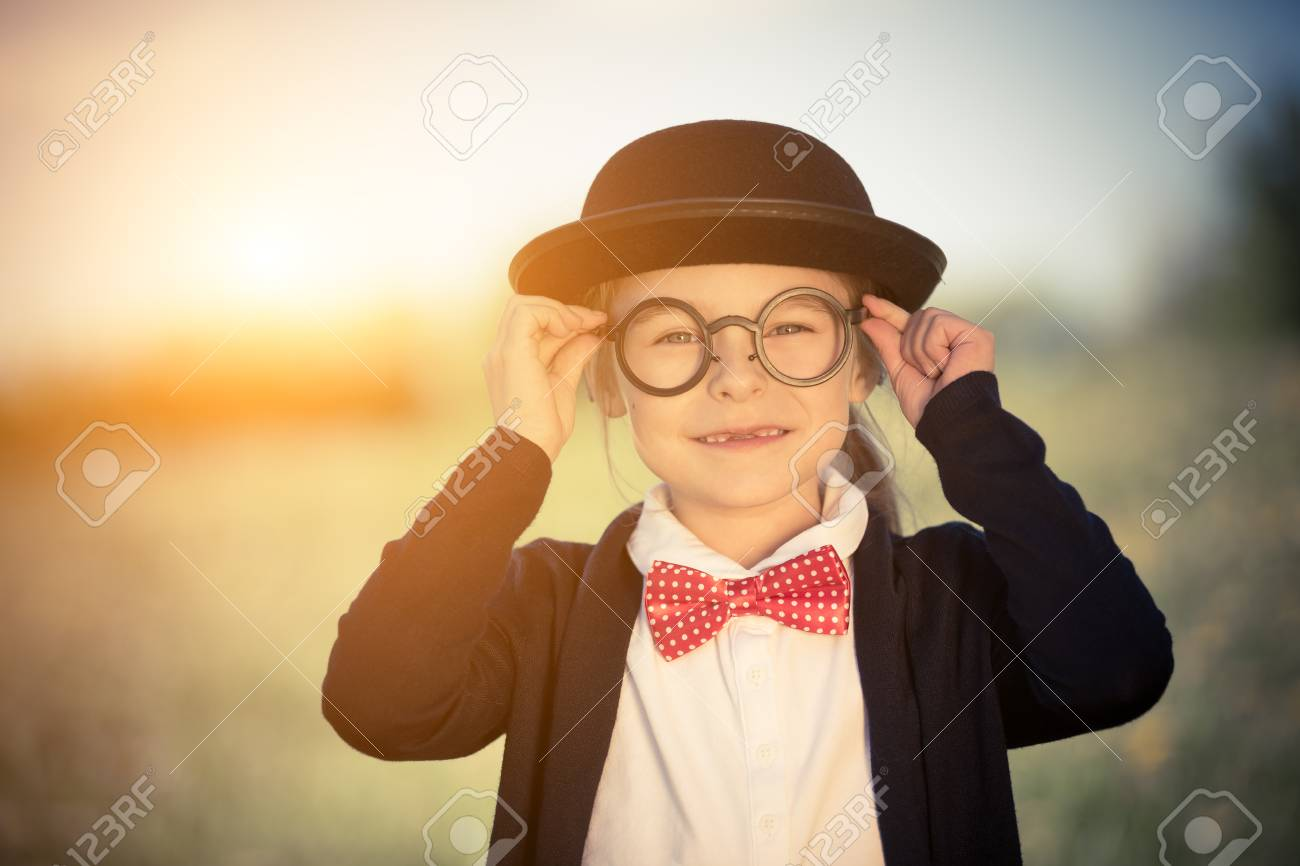 6c2c3db5bfb3 Outdoor portrait of funny little girl in glasses, bow tie and bowler hat.  Retro