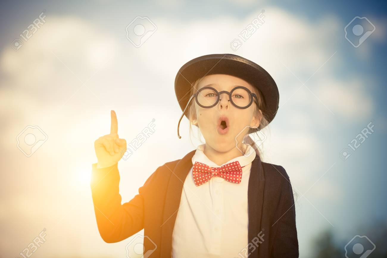 92bad25bff12 Outdoor portrait of funny little girl in glasses, bow tie and bowler hat  pointing finger