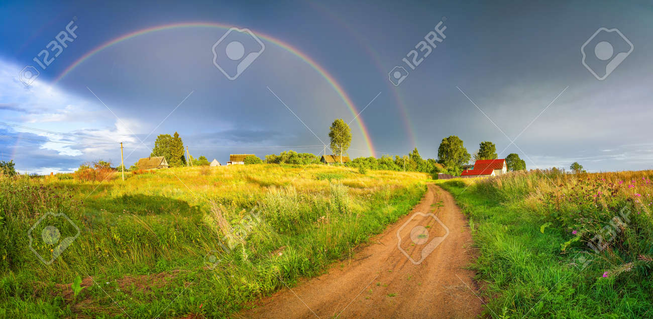 Rainbow over stormy sky. Rural landscape with rainbow over dark stormy sky in a countryside at summer evening. - 166253065