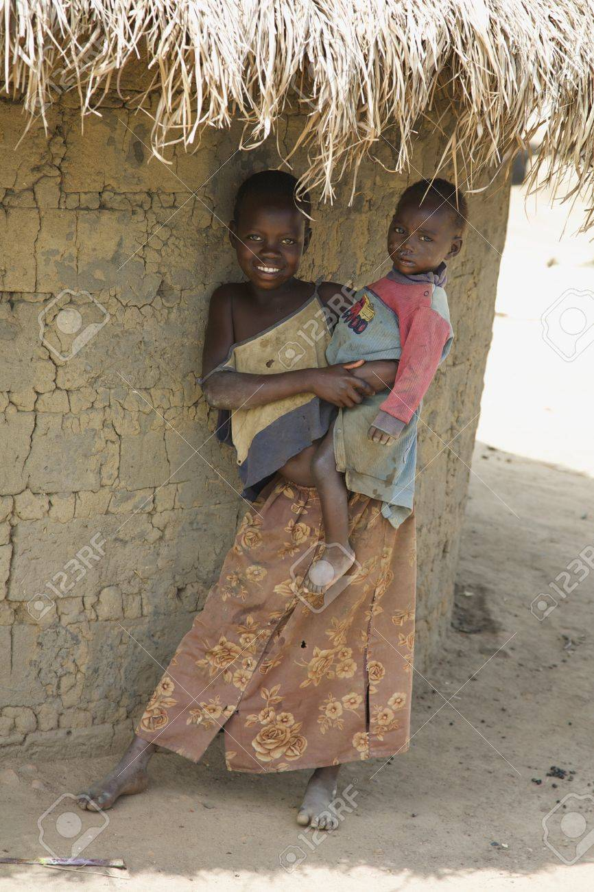 LIRA, UGANDA - JUNE 9: An unidentified girl holds her baby brother under thatched roof of their hut in Lira, Uganda on June 9, 2007. UNHCR estimates there to be over 136,000 refugees in Uganda. Stock Photo - 11748814