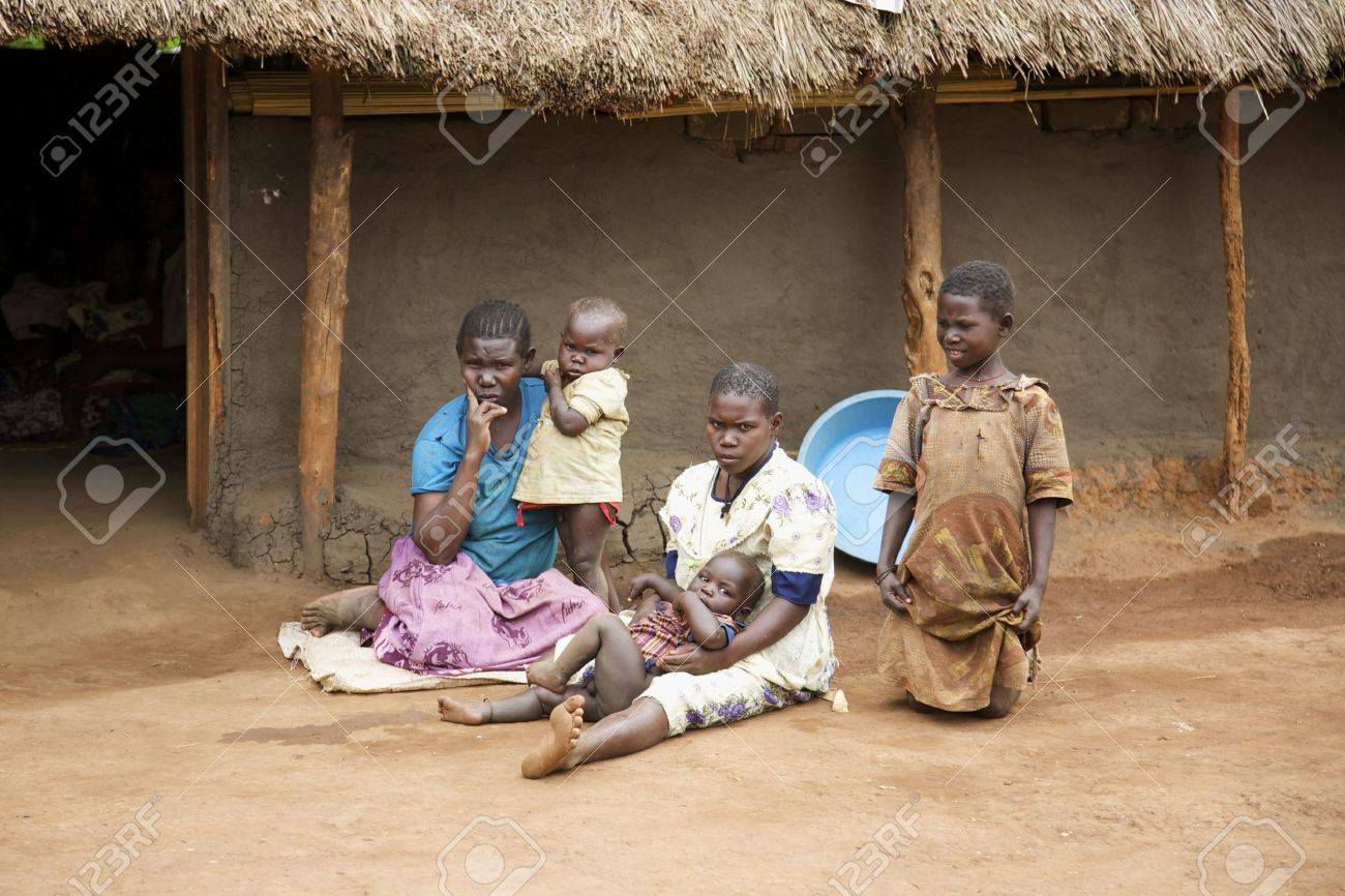 Lira, Uganda - June 9, 2007: A family outside their thatched roof hut in Lira, Uganda on June 9, 2007 Stock Photo - 11748815