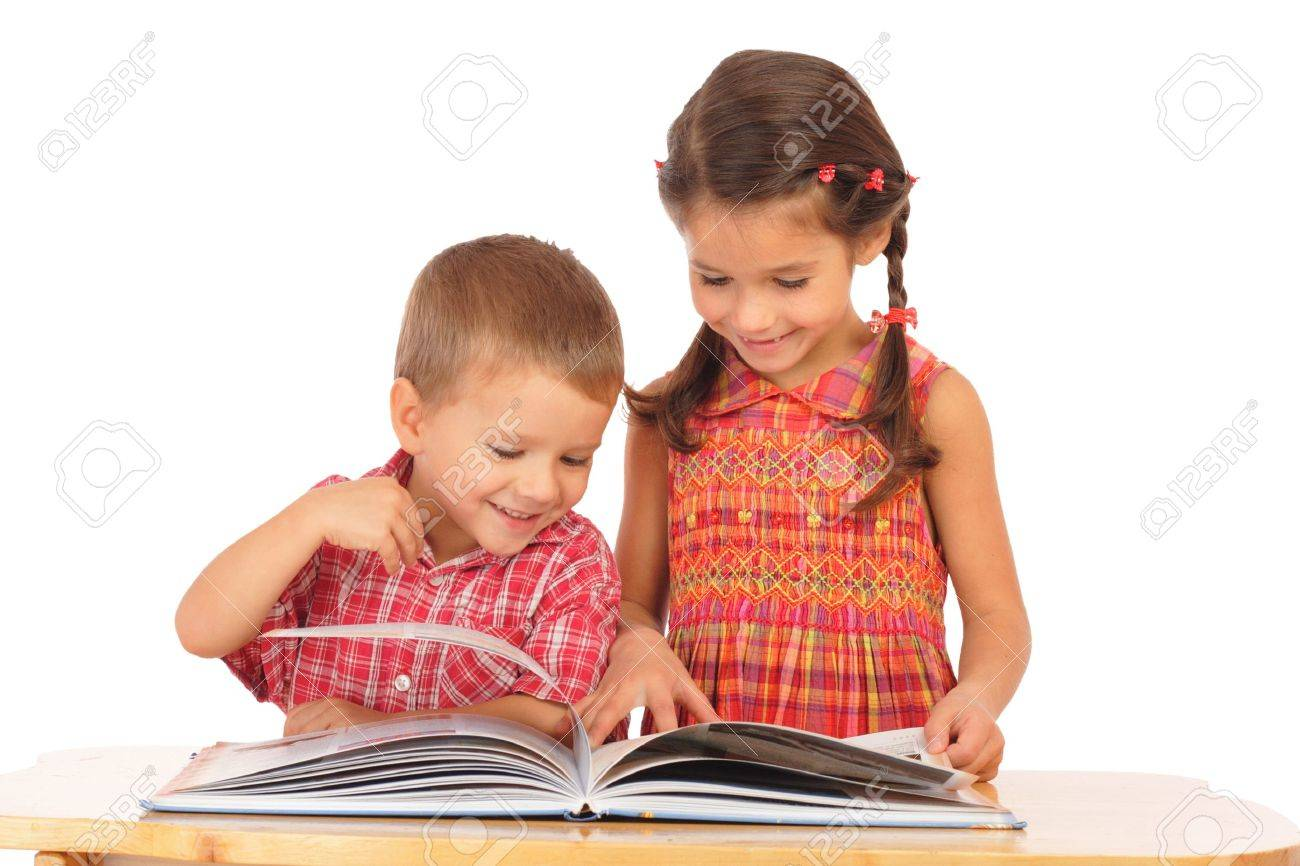 Two smiling children reading the book on the desk Stock Photo - 9144811