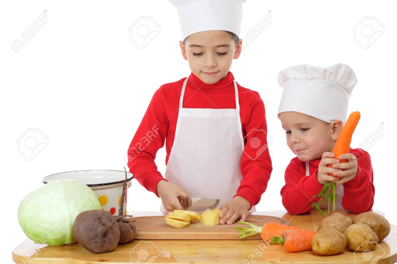Smiling little chief-cookers on the desk with vegetables, isolated on white Stock Photo - 9369377