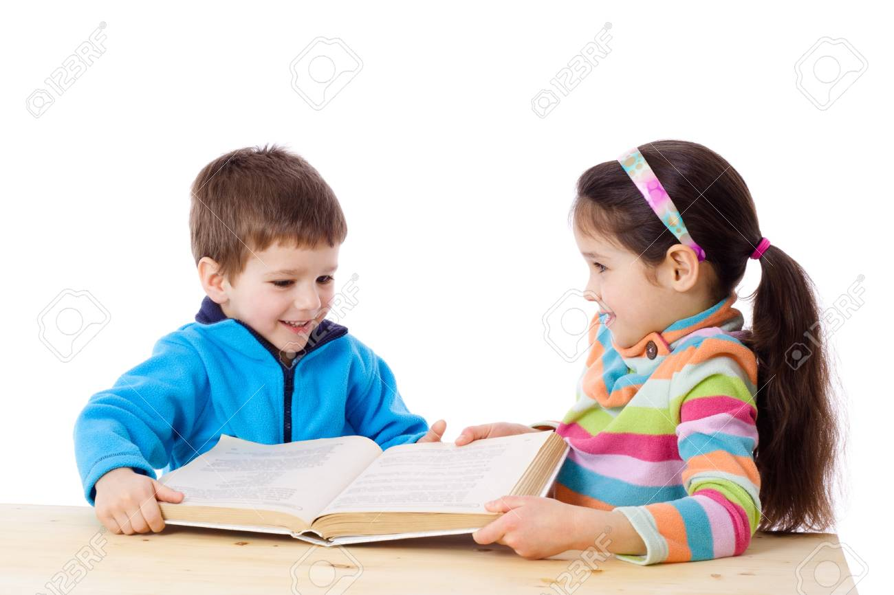 Two kids at the table sharing the book, isolated on white Stock Photo - 14402366