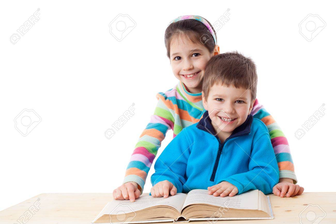 Two kids at the table reading the book together, isolated on white Stock Photo - 15044203