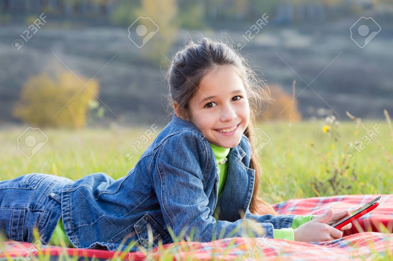 Smiling girl with tablet pc on the autumn landscape, outdoors Stock Photo - 22871651