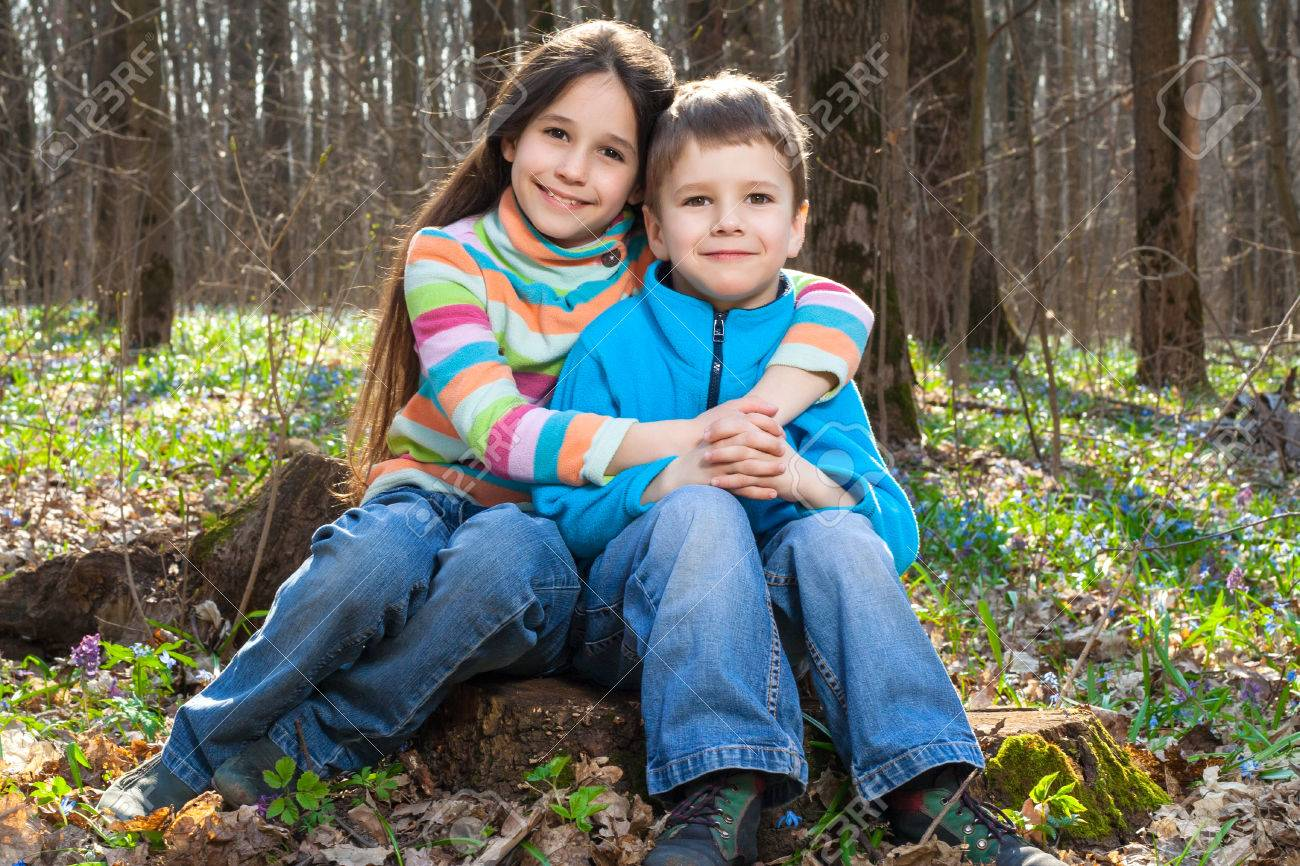 Two Kids Together Sitting In The Spring Forest Among Bluebells ...