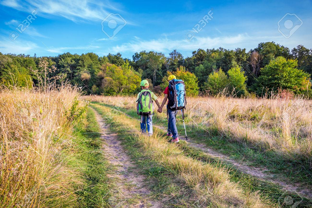 Two Kids With Backpacks Traveling Through A Meadow Stock Photo