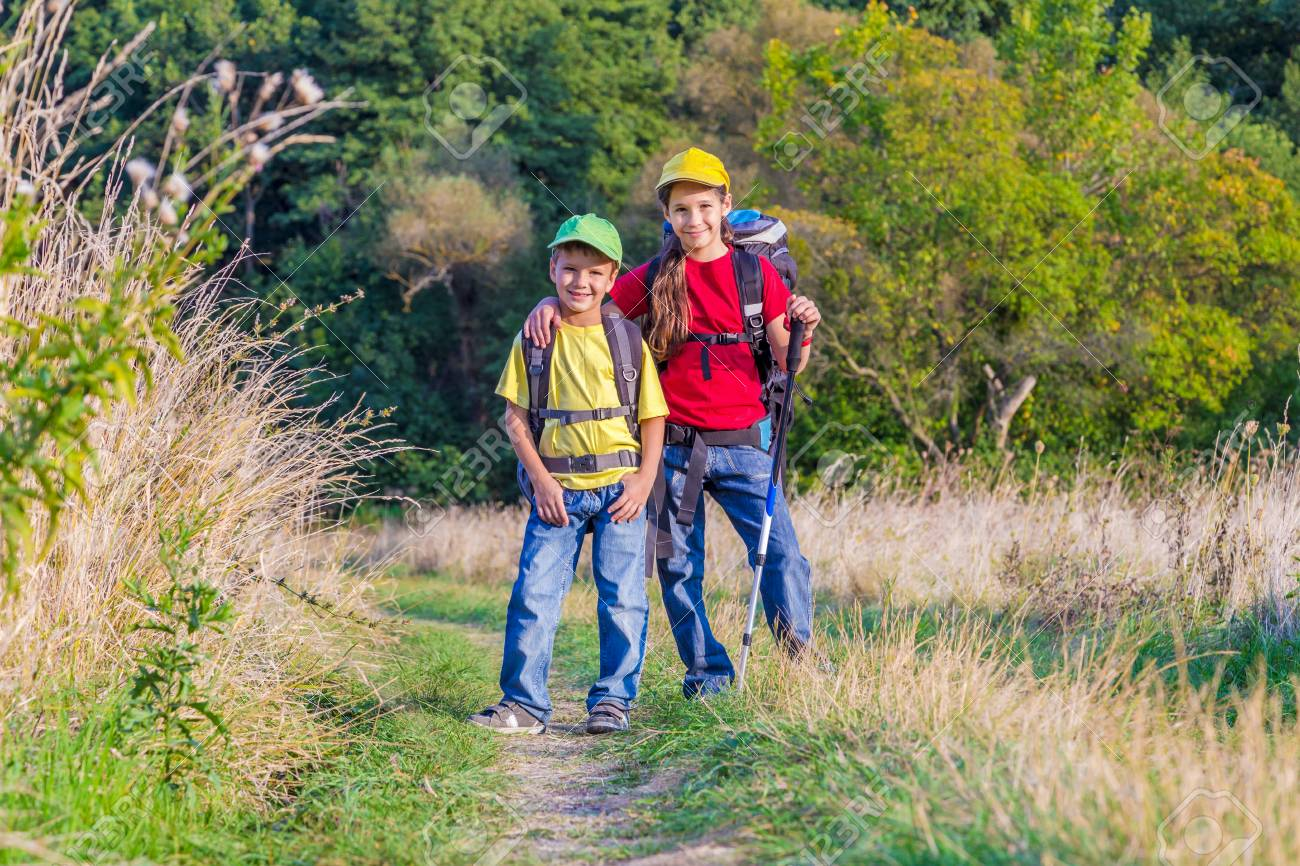 Two Kids With Backpacks Traveling Together Through A Meadow Stock