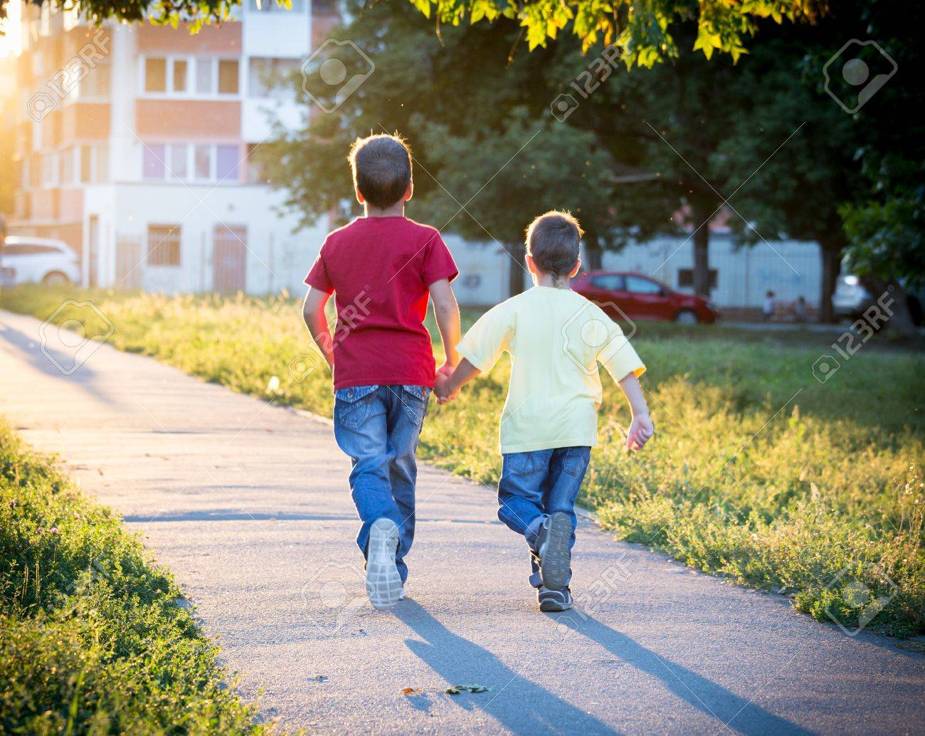 Two Boys Running Together On Street With Sun Back Light Stock Photo,  Picture And Royalty Free Image. Image 62710991.