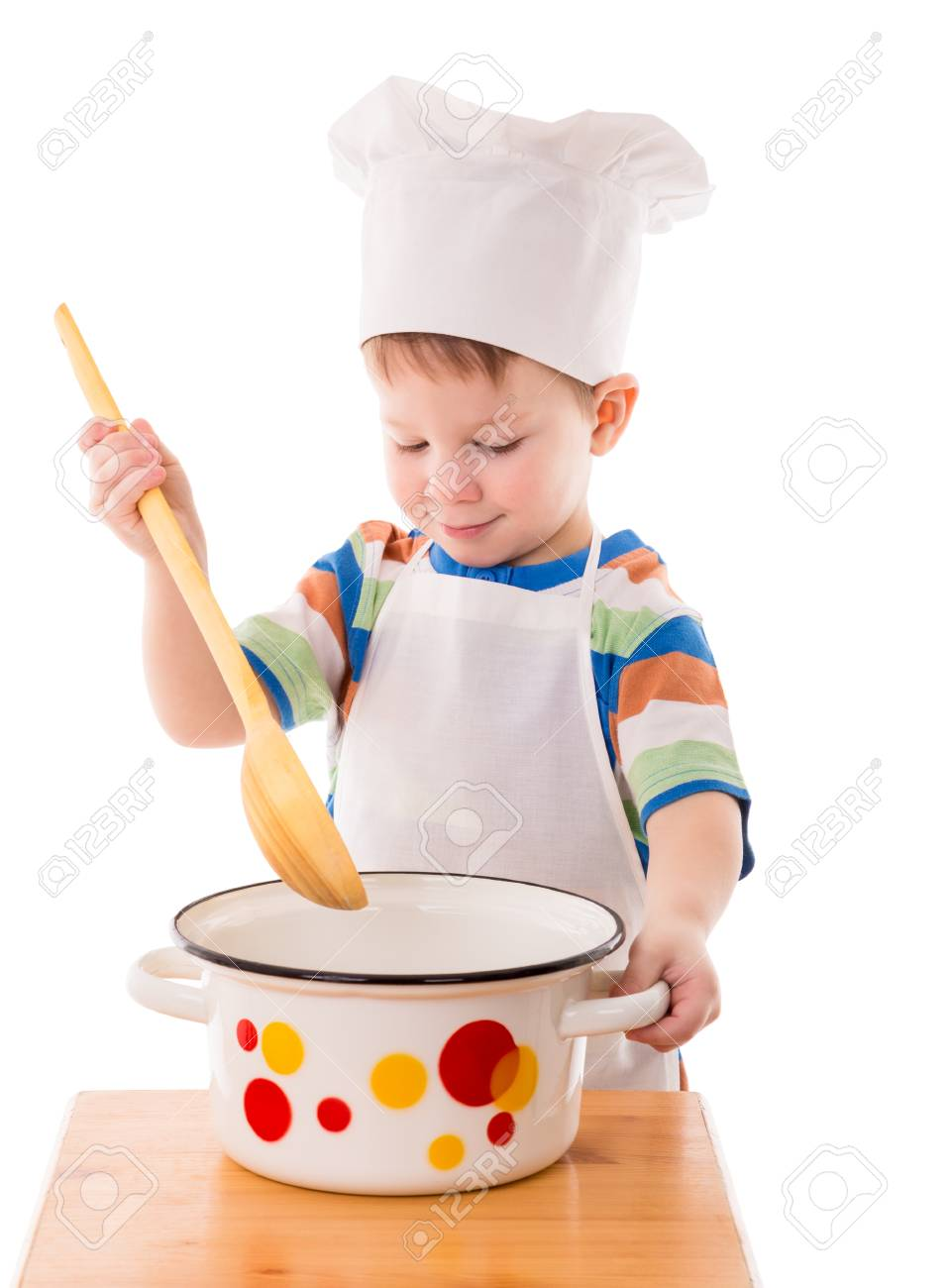 1783795caae Little boy with a big ladle in hand is mixing something from pan Stock  Photo -