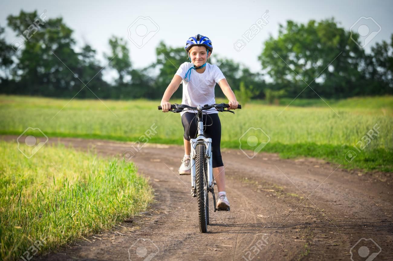 Smiling girl ride on bike on rural landscape - 100606828
