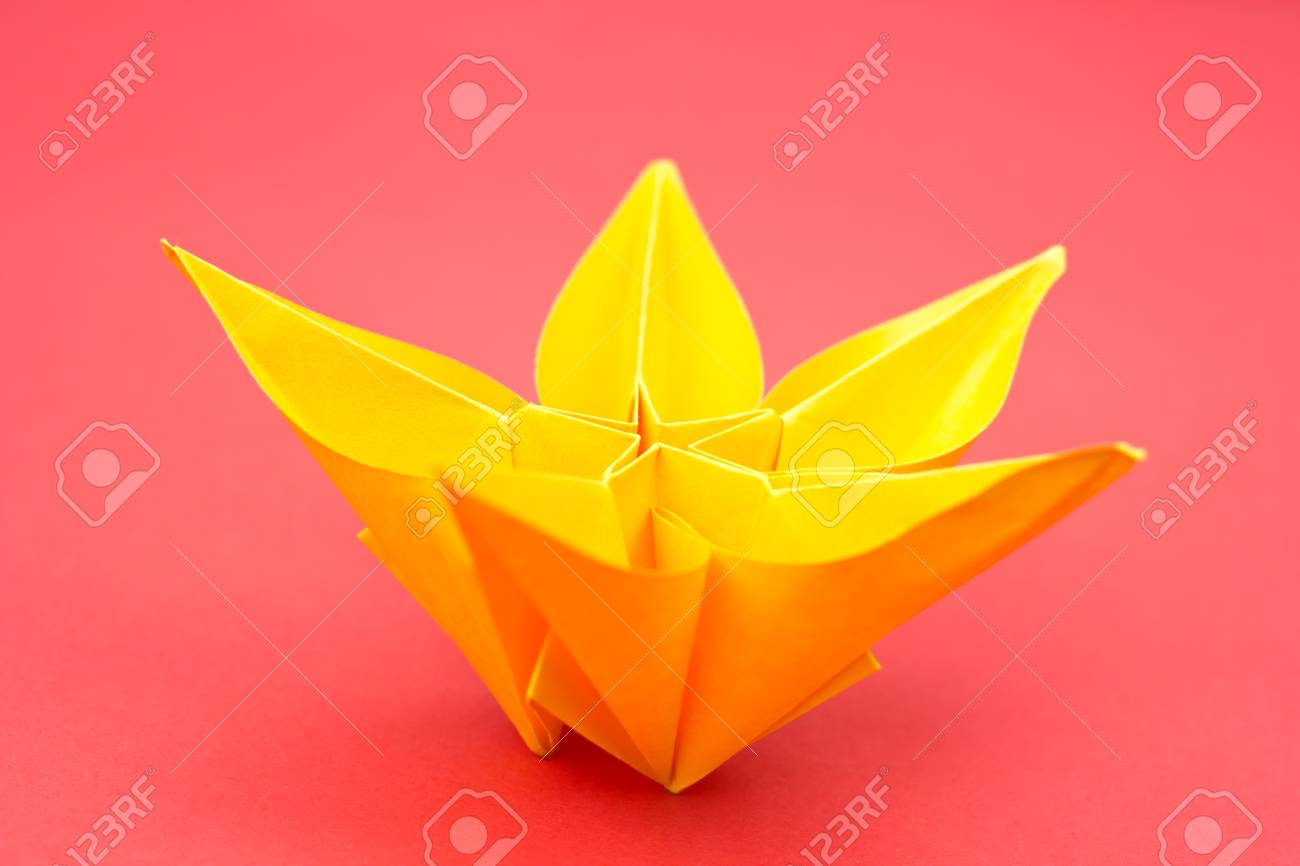 Yellow Paper Origami Flower On Red Background Stock Photo Picture