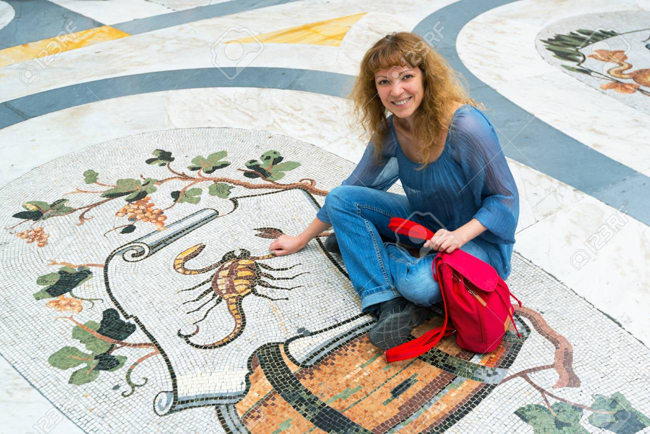 Young female tourist sitting on the image of the Zodiac sign Scorpio in Galleria Umberto I in Naples, Italy - 32974846