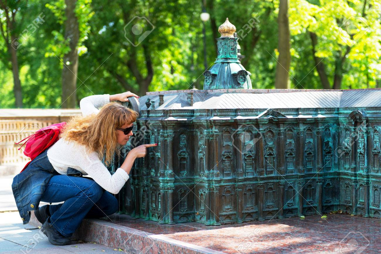 pretty tourist looks at a miniature replica of the winter palace