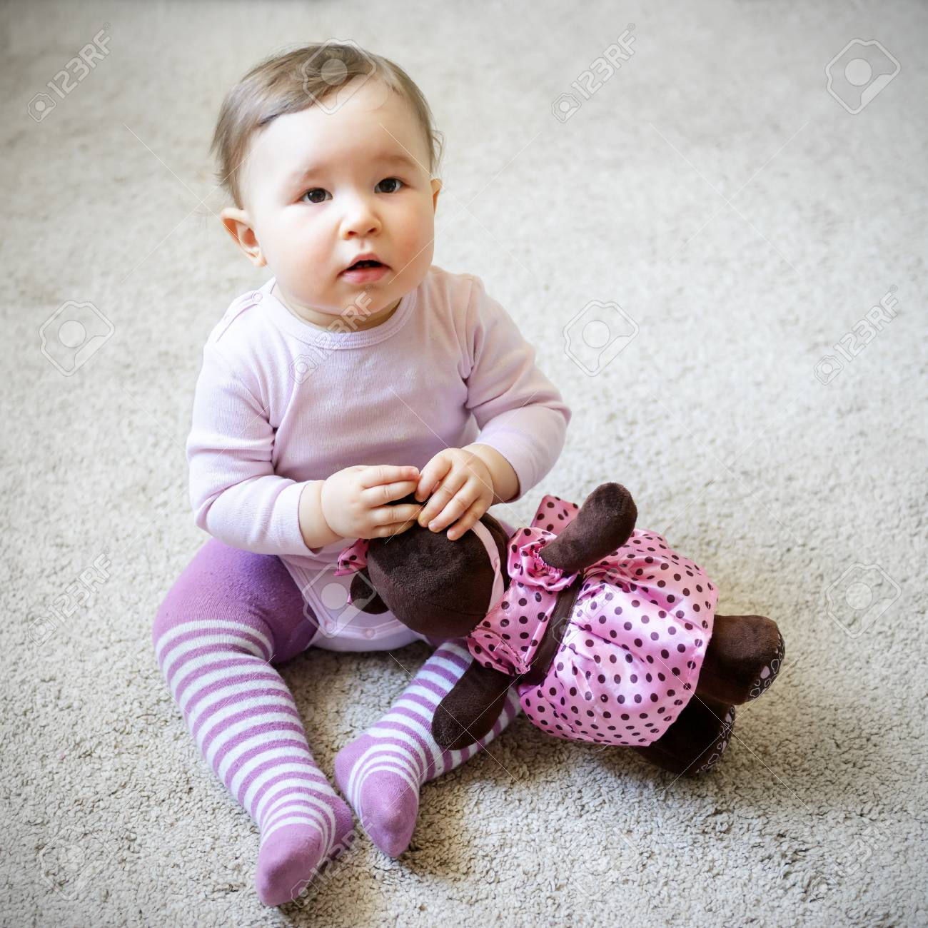 thoughtful and serious nice baby girl sitting on the floor with