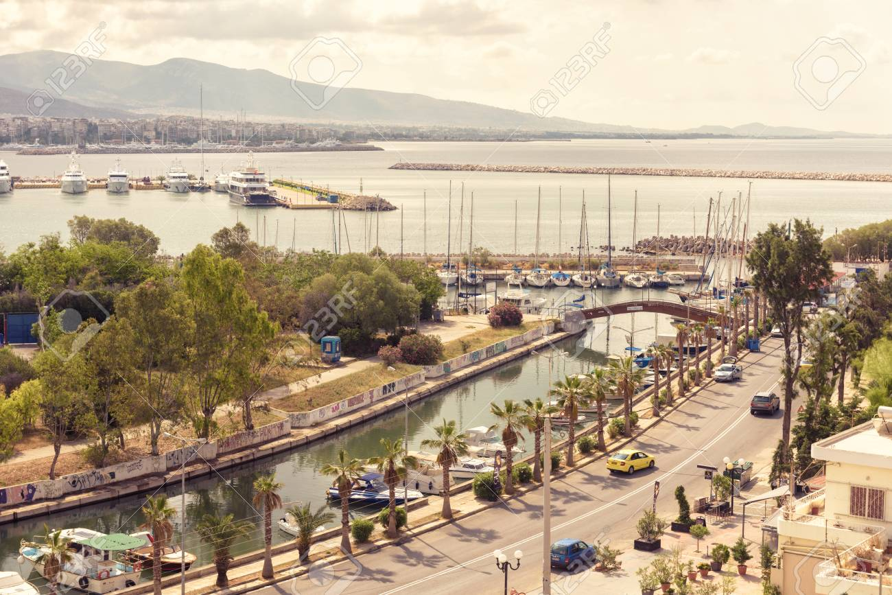 Athens - May 7, 2018: Waterfront in Piraeus, Greece. Scenic aerial view of a beautiful embankment with a canal and marina. Panorama of the city with a sea port. Sunny scenery of the coast of Athens. - 112425270