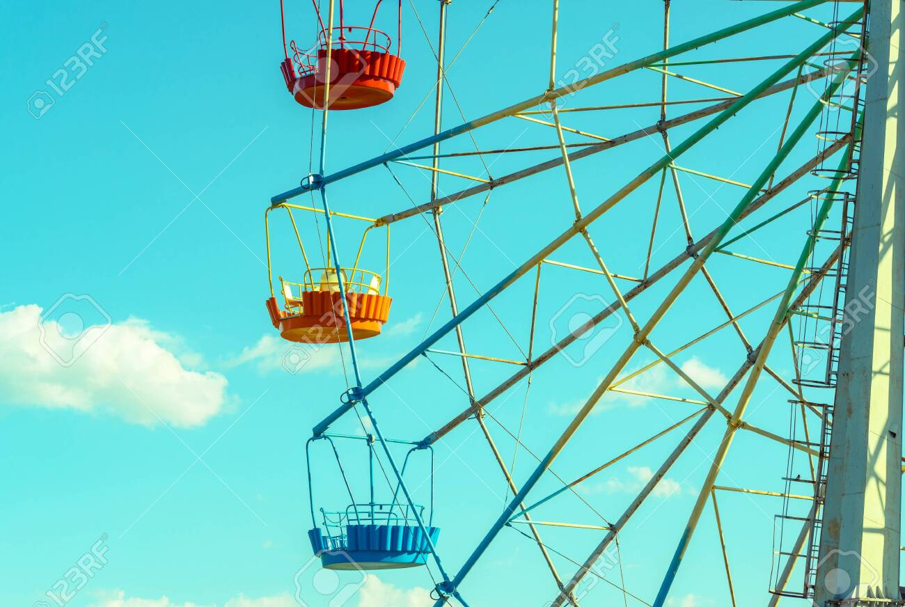 Ferris wheel with colorful cabins on the blue sky background. Detail of the colored Ferris wheel against clouds. Concept of holiday and kids amusement. - 126556355