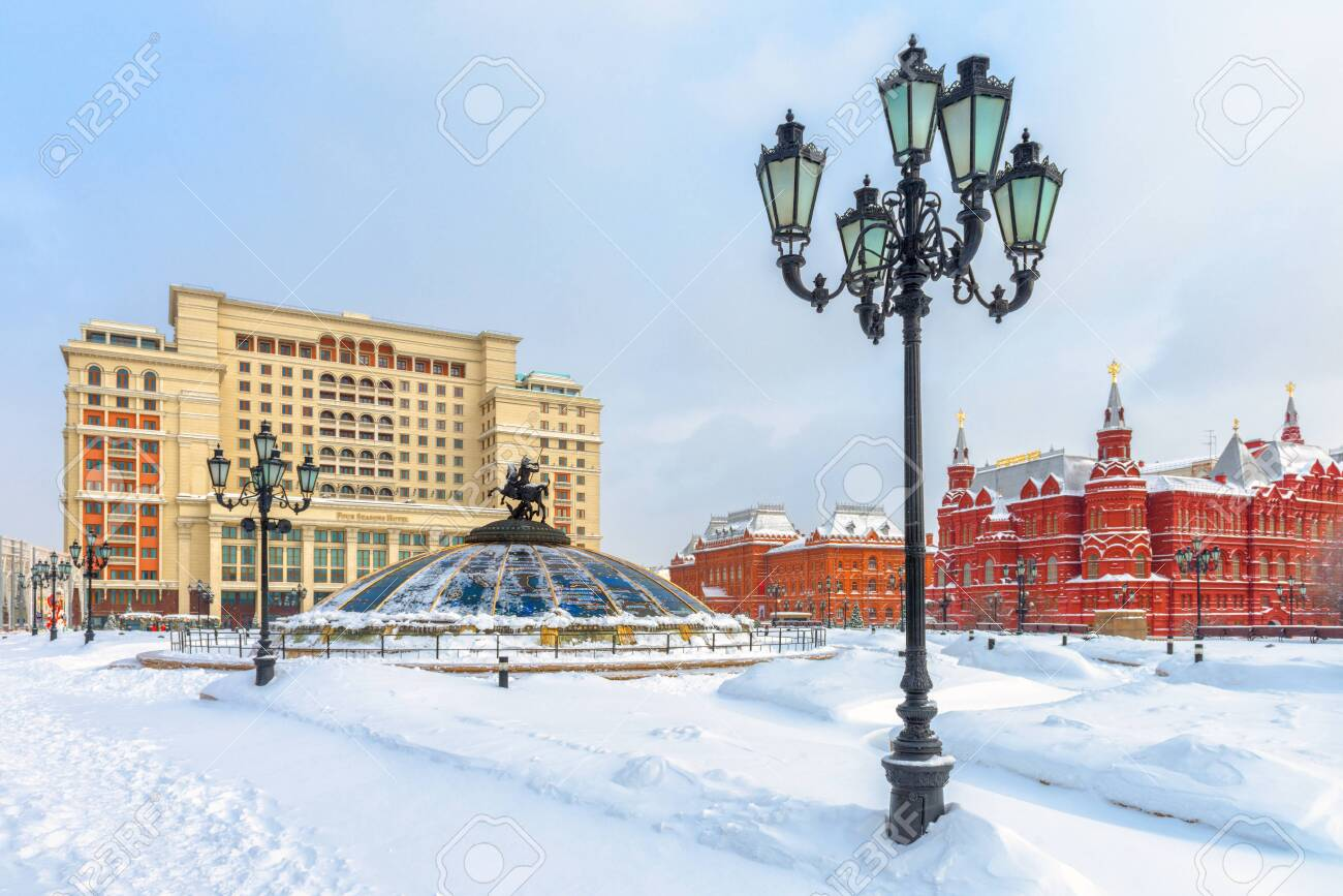 Moscow, Russia - Feb 5, 2018: Manezhnaya Square under snow in Moscow. Nice panoramic view of the snowy Moscow center in frosty winter. Dome with statue of St George and Four Seasons Hotel behind it. - 136649426