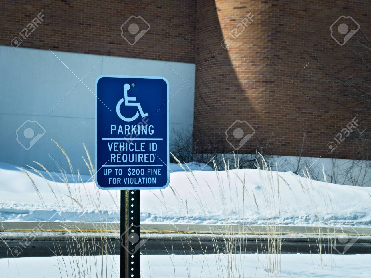Handicapped parking sign posted in snow covered parking lot in winter. - 142323391