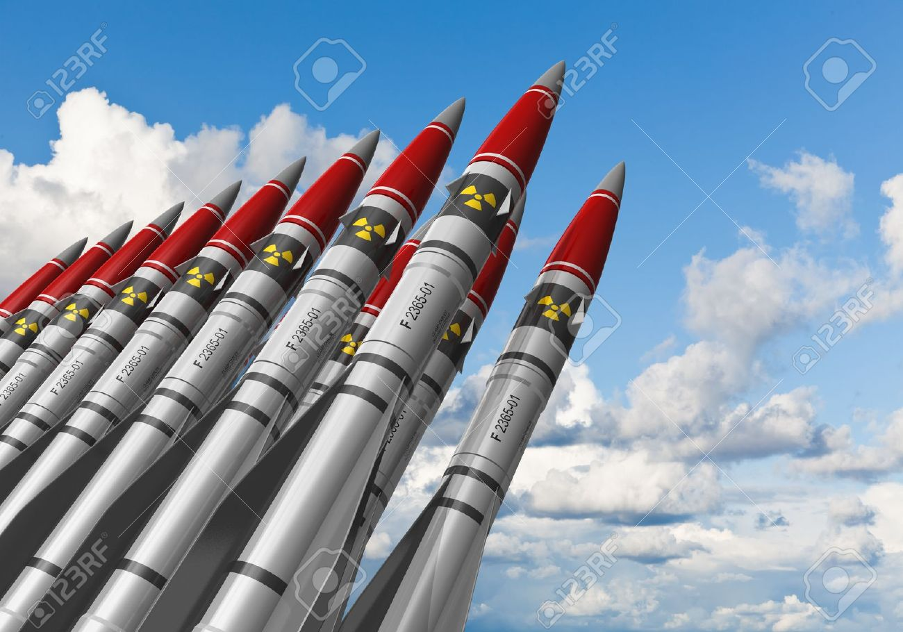 Row of heavy nuclear missiles against blue sky with clouds - 11907276