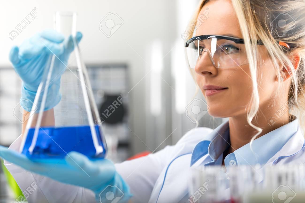 Banque d images - Heureux jeune femme séduisante scientifique avec des  lunettes de protection et des gants tenant un flacon avec une substance  liquide bleue ... cb9c18dcb724