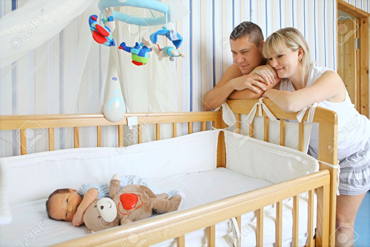 Baby bed in parents room - Happy Parents Near Baby S Bed Stock Photo 14793329