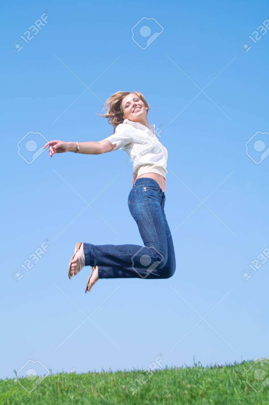 Beautiful lady in white shirt and jeans jumping Stock Photo - 3494526