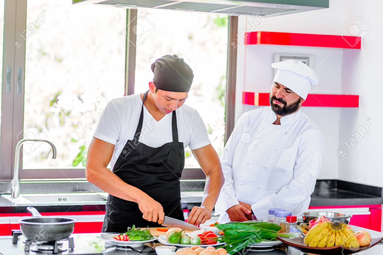 Colleagues At Work: Thai And European Chefs At The Kitchen Doing ...