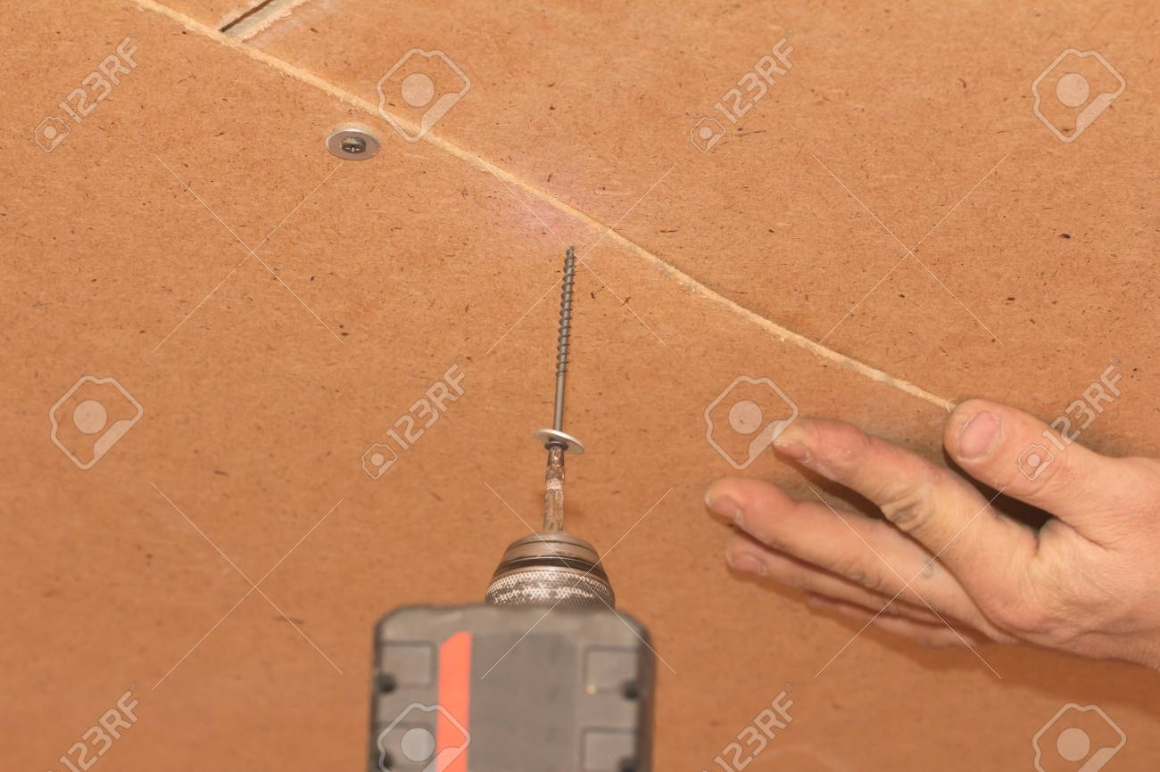 tightening the screws into the wood wall Stock Photo - 17366181
