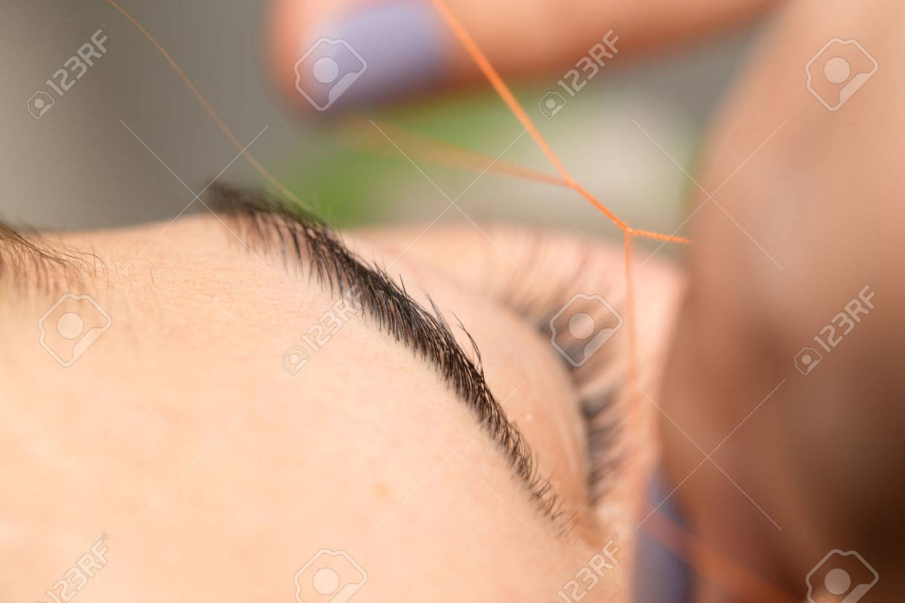 Grooming The Eyebrows Thread In A Beauty Salon Close Stock Photo
