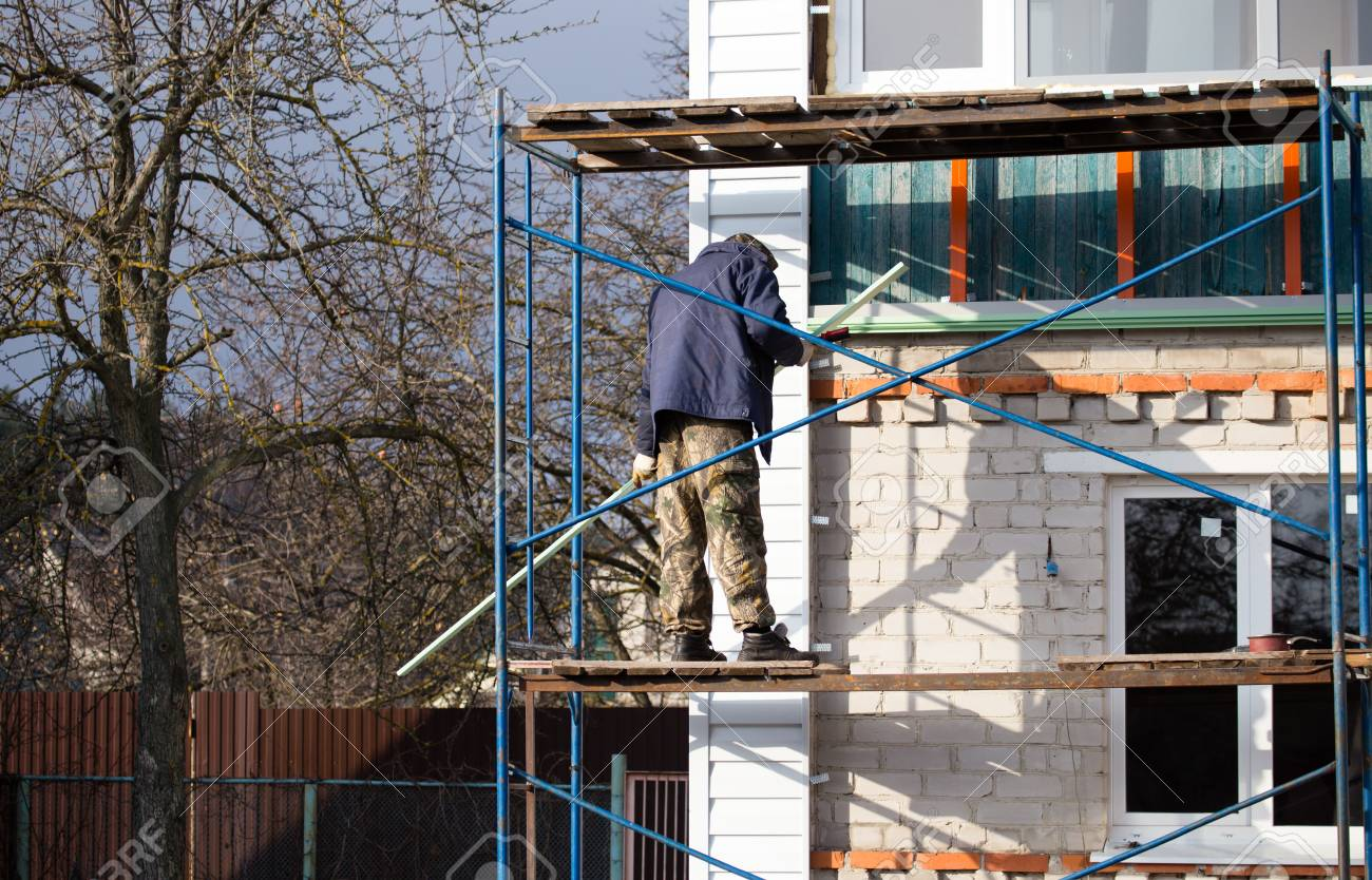 workers walling the house with wall siding stock photo picture rh 123rf com house with wall tiles house with walled garden for sale uk