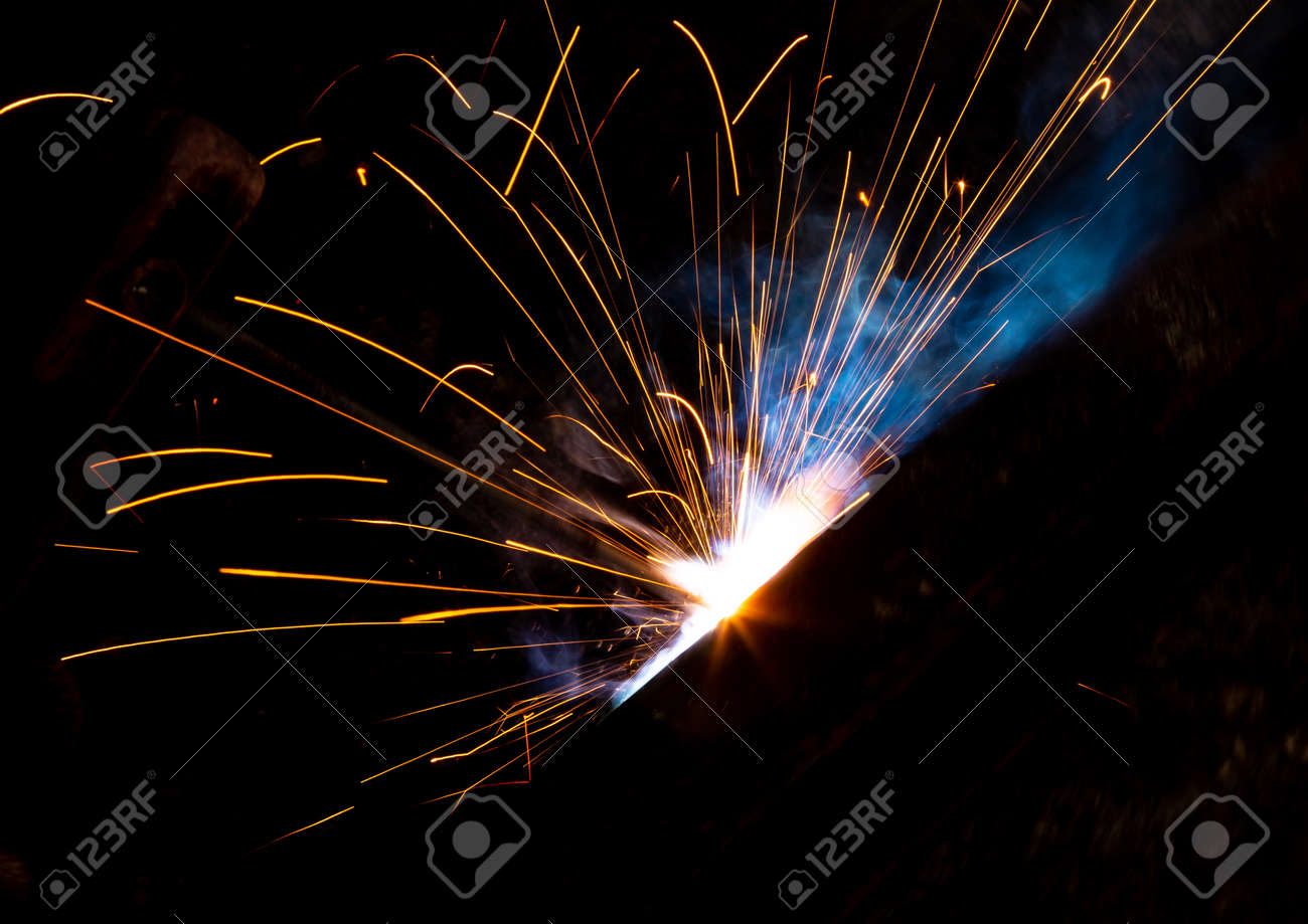 Sparks from welding at a construction site as a background. - 121802107