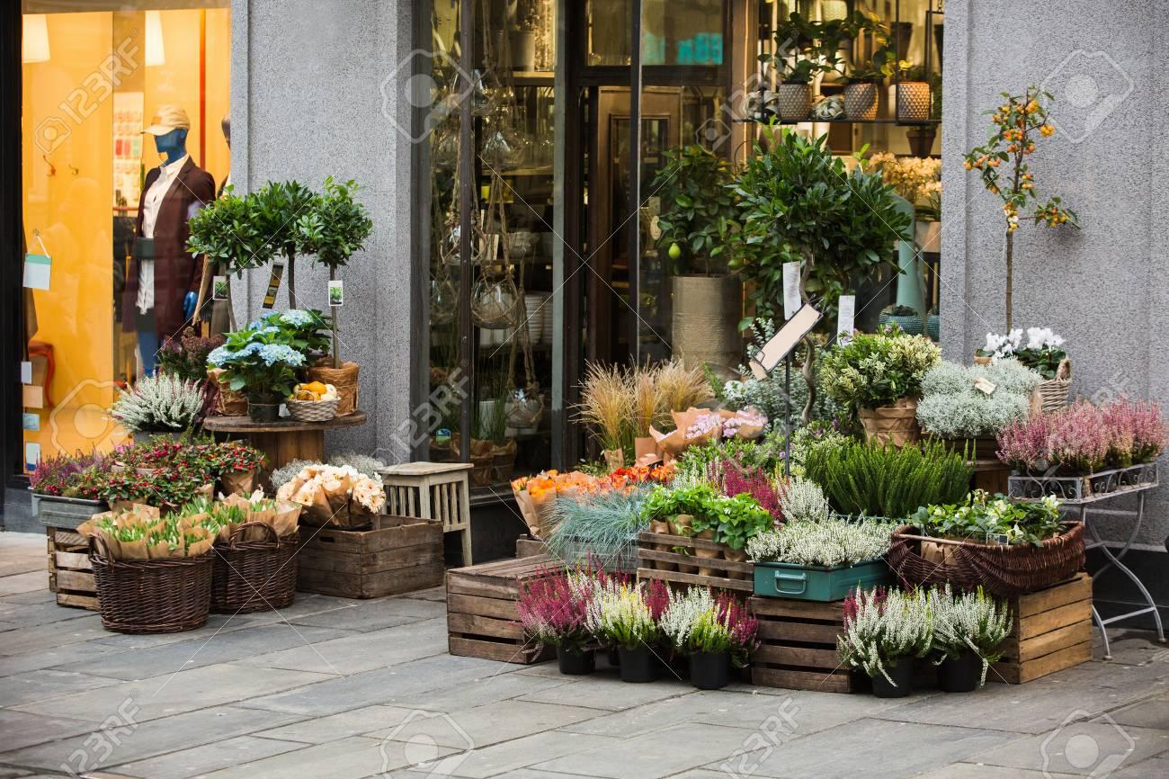 flowers are near a flower shop on a city street.