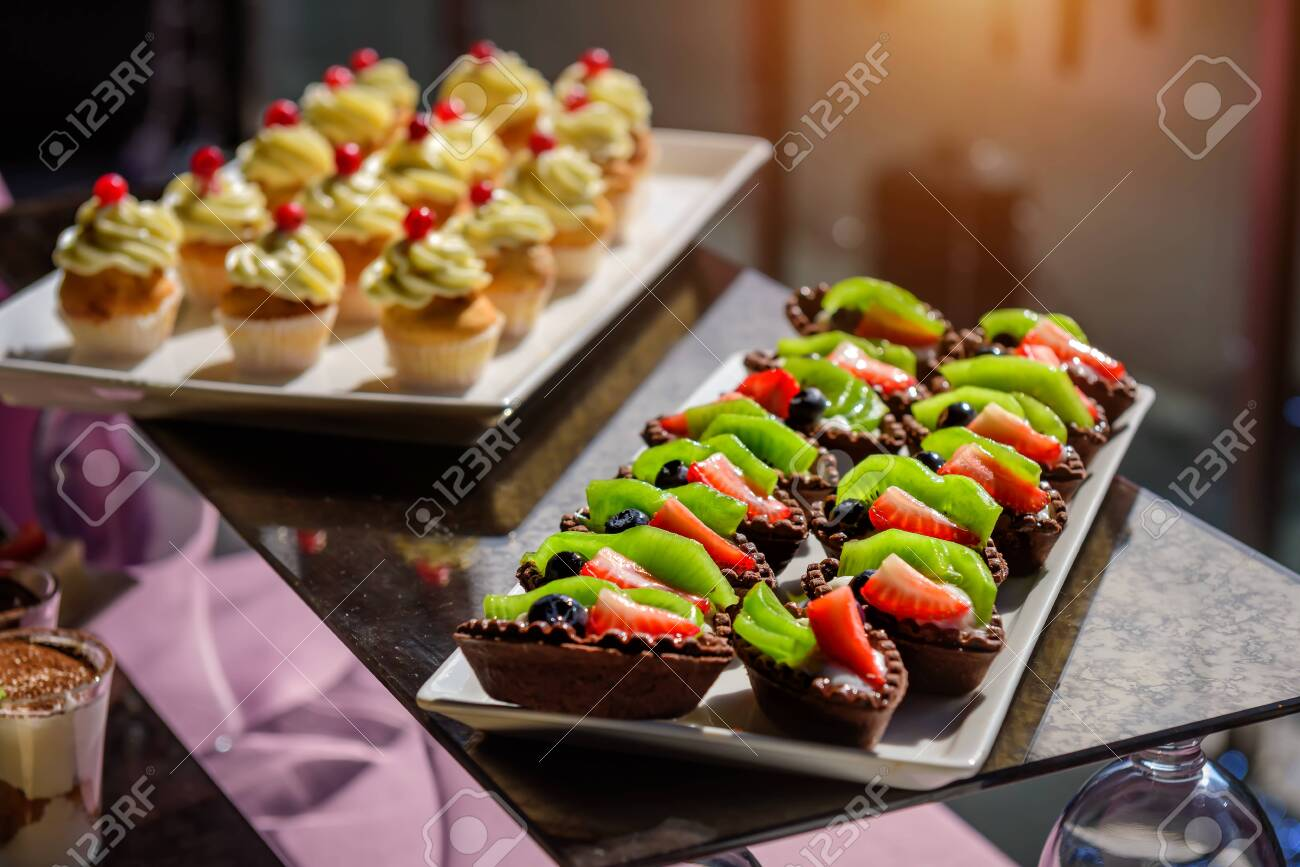Cakes with fresh fruit and berries on the holiday table, close-up. Cupcakes with cream. Sweet table at gala dinner. - 146417925