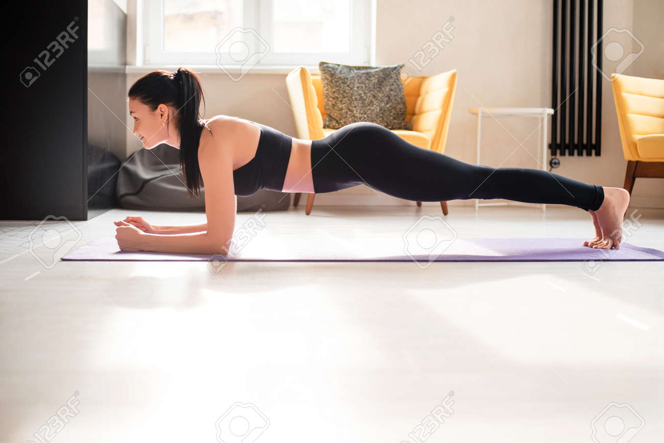 Beautiful strong woman in sport clothes standing in plank position on yoga mat. Active brunette doing abs exercises while staying at home. - 166548929