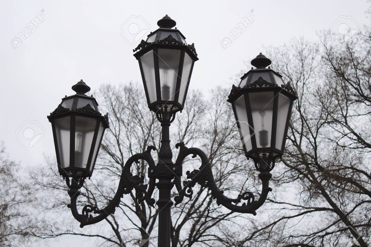 Vintage triple street lamp at cloudy day - 25100867