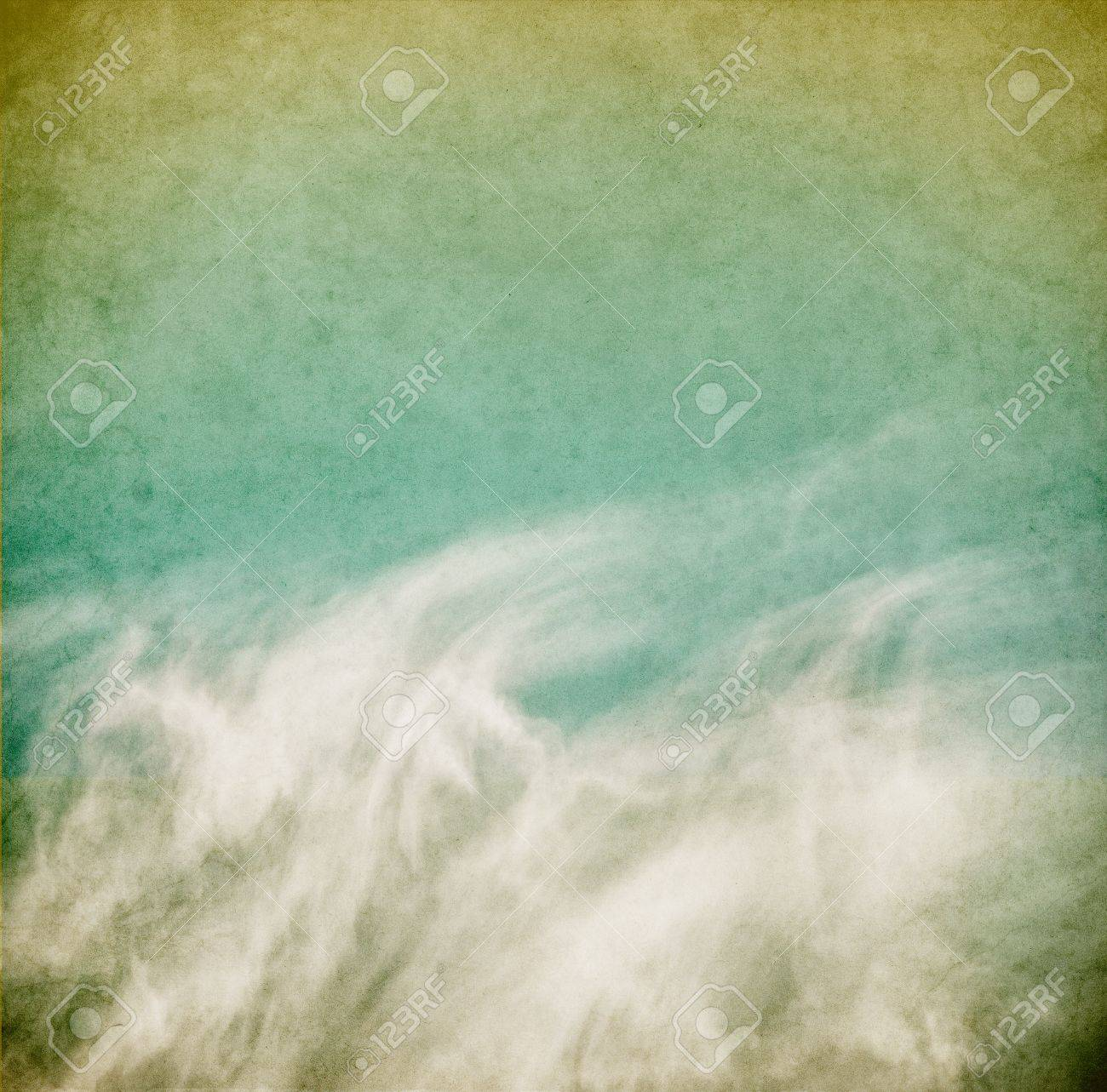 Wispy spring clouds on a textured, vintage paper background with grunge stains. Stock Photo - 12782122