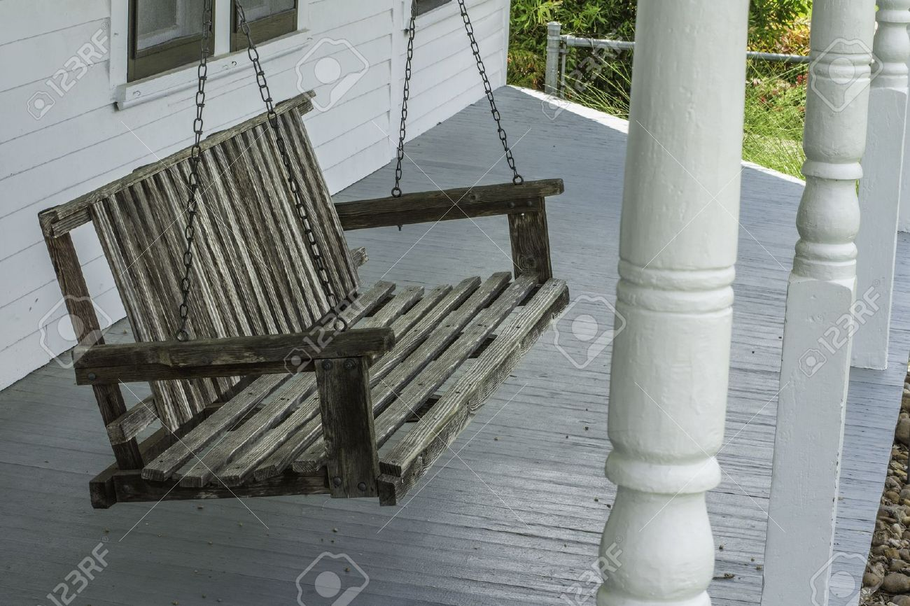 old wooden porch swing hanging on a front porch of an old home stock photo - Front Porch Swing