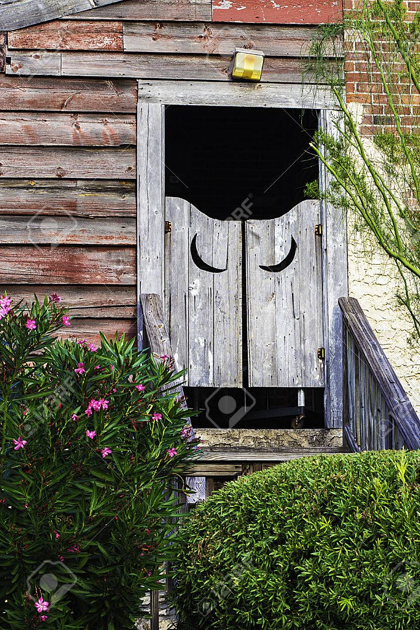 A view of outhouse doors with crescent moons carved into the wood Stock Photo - 22797462