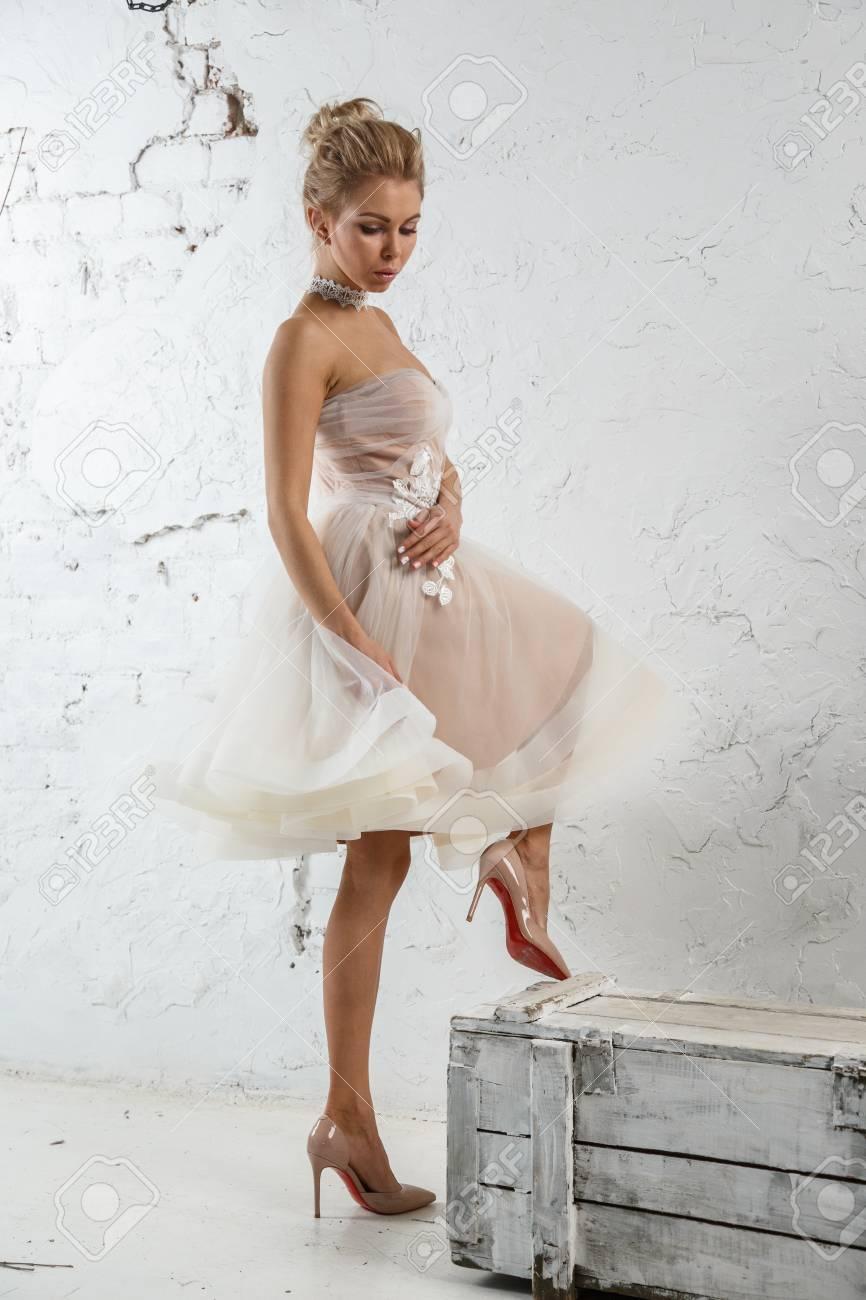 Schöne Sexy Blonde Frau Im Weißen Kleid Posiert Gegen Weiße Wand ...